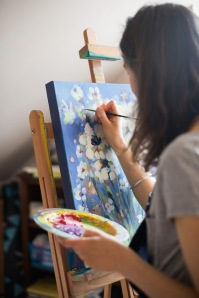 artist-painting-at-easel-flowers-palette-pretty